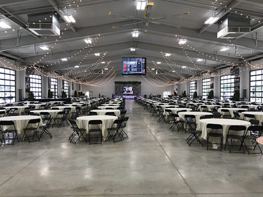 A photograph of Interior of the Peter B. Orthwein Pavilion at the RV/MH Hall of Fame in Elkhart, Indiana. There are 40+ round tables lined up in neat rows. The tables have folding chairs arranged around them. There are strings of white lights decorating the ceiling of the hall. A stage is located across the room from where the camera is set up.