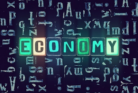 "A picture of different green tile letters spelling out the word ""economy"" with other letters scattered on a black surface behind."