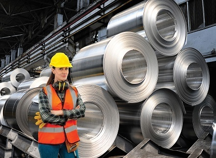 A picture of a woman in construction gear standing in front of about a dozen big rolls of sheet metal stacked up in several piles