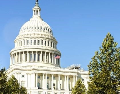 A picture of part of the U.S. Capitol Building in front of a clear blue sky. The American flag is flapping in the wind.
