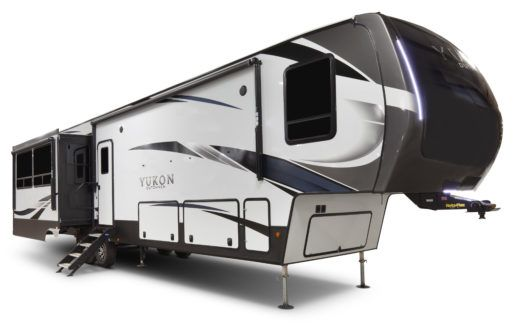 A picture of a Dutchmen Yukon 2020 400RL fifth wheel in front of a white background. The steps are extended and the slidout is out.