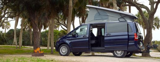 A picture of a Mercedes-Benz Metris Weekender camper van with the top popped up next to a camp fire at a camp site. Palm trees and other foliage are in the background.