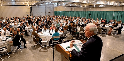 A photograph from the stage's perspective of a man standing at a podium addressing a conference hall full of people. This is the Recreational Vehicle and Motorhome Hall of Fame Induction Dinner