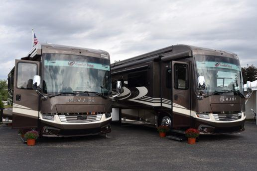 Picture of Newmar 2020 type a motorhomes parked on asphalt with flower planters on the ground beside them. The sky is cloudy in the background.